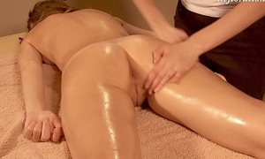 Elena being oil massaged by another spread out